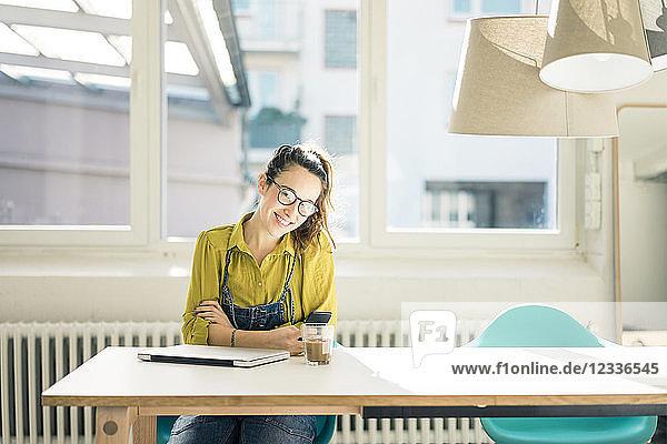 Smiling freelancer sitting at desk in her studio