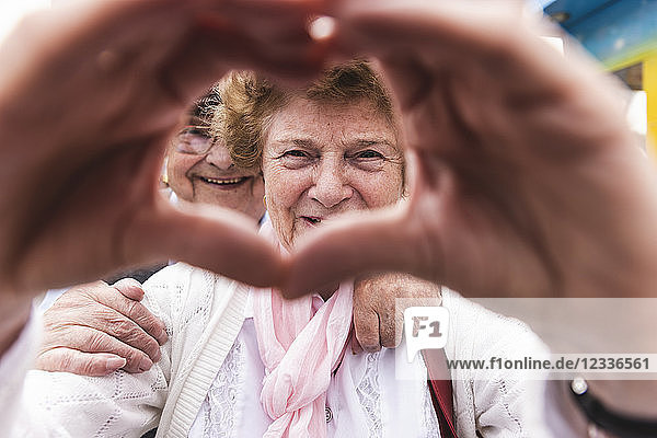 Portrait of happy senior woman shaping heart with her hands