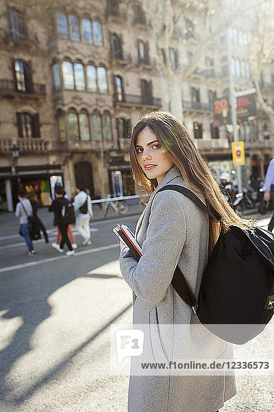 Spain  Barcelona  portrait of young woman with backpack standing at street