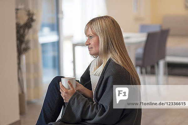 Woman sitting at home  drinking coffee