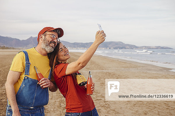 Couple with soft drinks taking selfie with smartphone on the beach