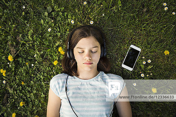 Portrait of girl lying on meadow listening music with headphones and smartphone