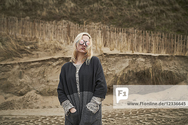 Fashionable blond young woman wearing mirrored sunglasses on the beach