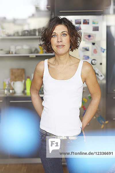 Portrait of mature woman wearing white tank top standing in the kitchen