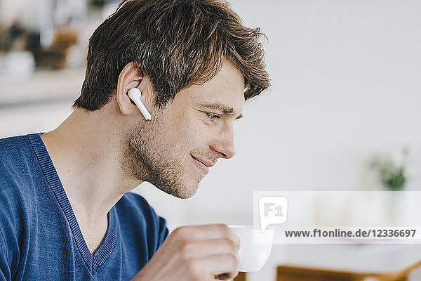 Smiling man in a cafe with earphone drinking coffee