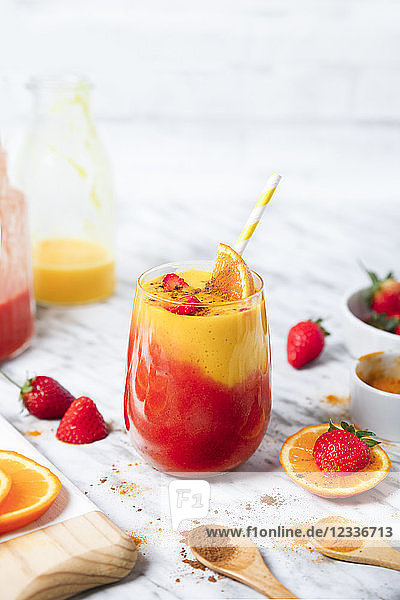 Strawberry and orange smoothie with curcuma and cinnamon on marble