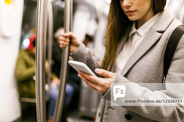 Businesswoman using cell phone in underground train  partial view