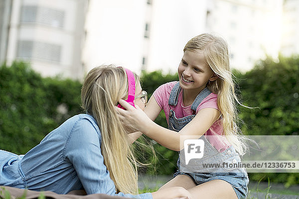 Happy mother and daughter listening to music together in garden