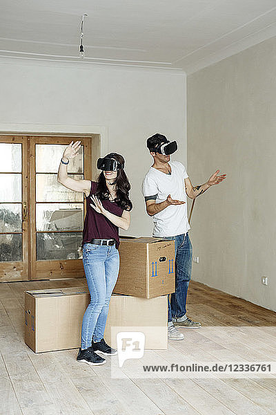Couple moving into their new home  looking through VR glasses