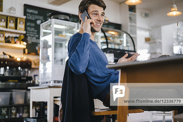 Smiling man in a cafe on cell phone