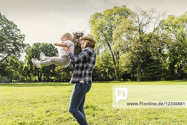 Happy mother lifting up son in a park