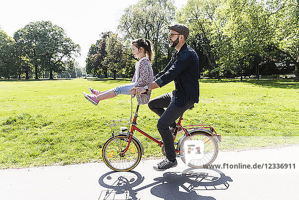 Happy father riding bicycle with daughter sitting on handlebar in a park