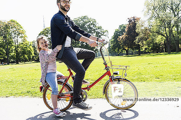 Happy father riding bicycle with daughter in a park