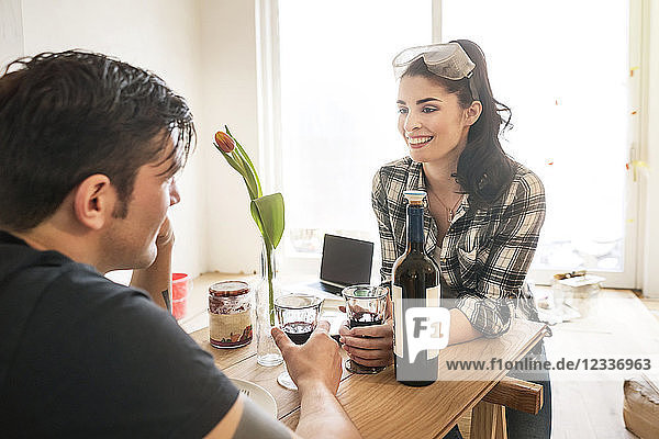 Couple renovating their flat  taking a break  drinking red wine