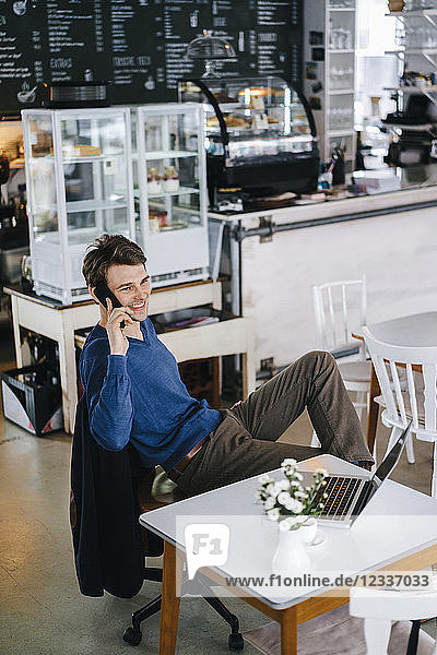 Smiling man in a cafe with laptop on cell phone