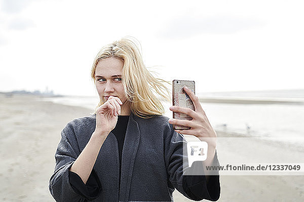 Netherlands  portrait of blond young woman taking selfie with smartphone on the beach