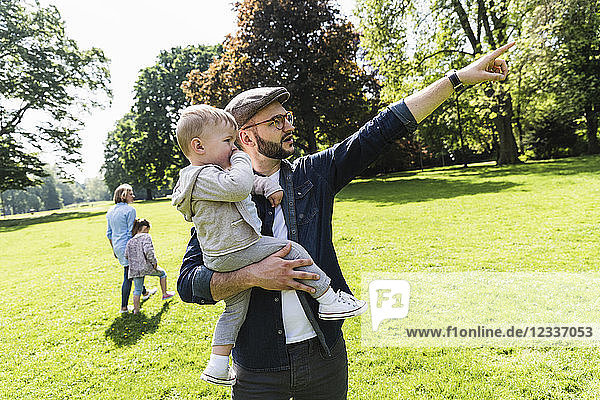 Father carrying and talking to son in a park