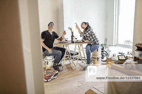 Happy couple renovating flat  taking a break  talking