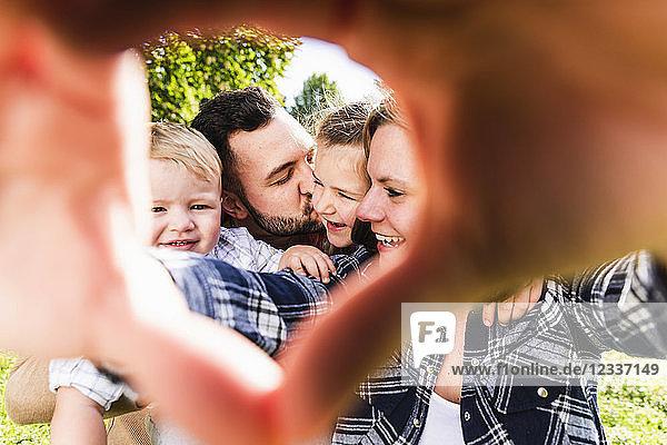 Happy family behind finger frame