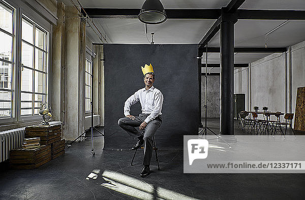 Portrait of mature businessman with crown in front of black backdrop in loft