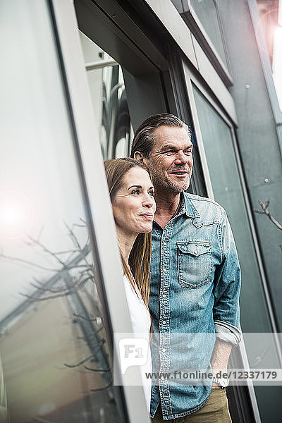Smiling couple looking out of window