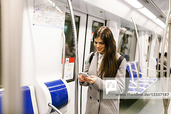 Spain  Barcelona  young woman in underground train looking at cell phone
