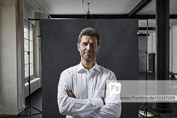 Portrait of mature businessman in front of black backdrop in loft