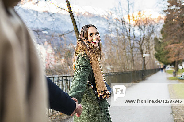 Austria  Innsbruck  portrait of happy young woman strolling hand in hand with her boyfriend at winter time