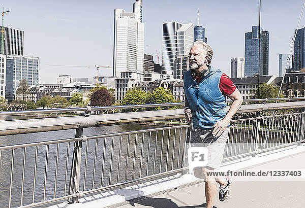 Smiling mature man with headphones running on bridge in the city