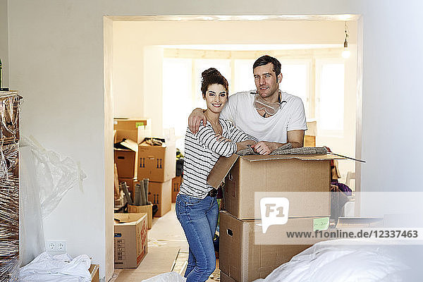 Young couple moving house  unpacking cardboard boxes