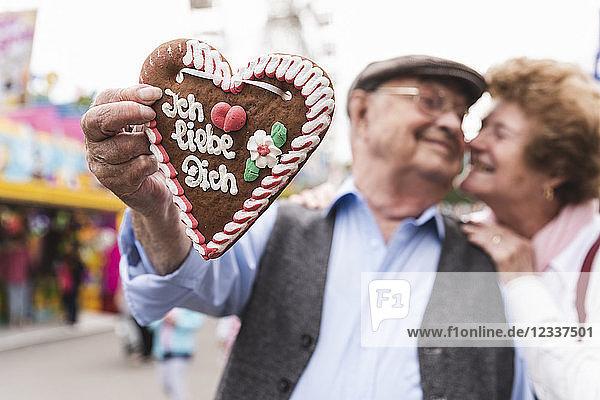 Hand of senior man holding ingerbread heart on fair  close-up