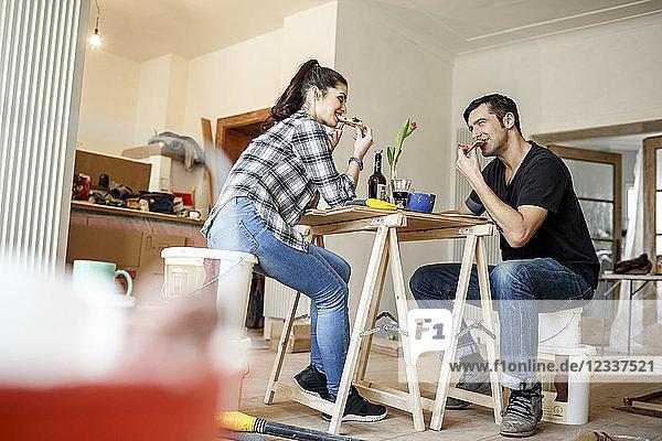Happy couple renovating flat  taking a break