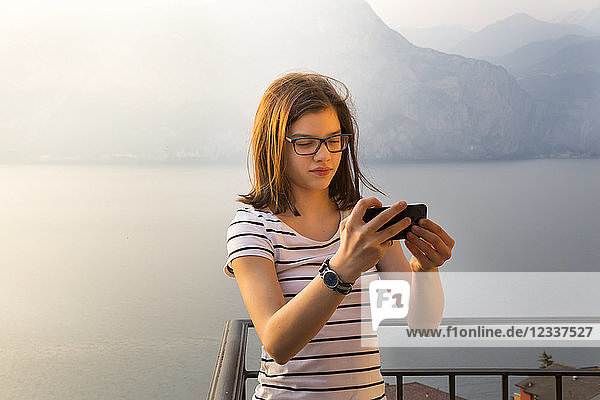 Italy  Brenzone  portait of girl taking selfie with smartphone on balcony