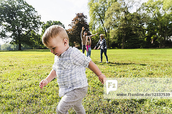 Boy walking in a park with family in background