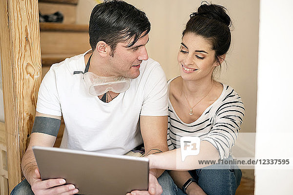 Young couple refurbishing new home  sitting on stairs using digital tablet