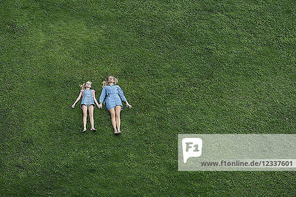 Bird's eye view of mother and daughter lying in garden holding hands