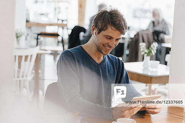 Smiling man in a cafe with earphone using tablet