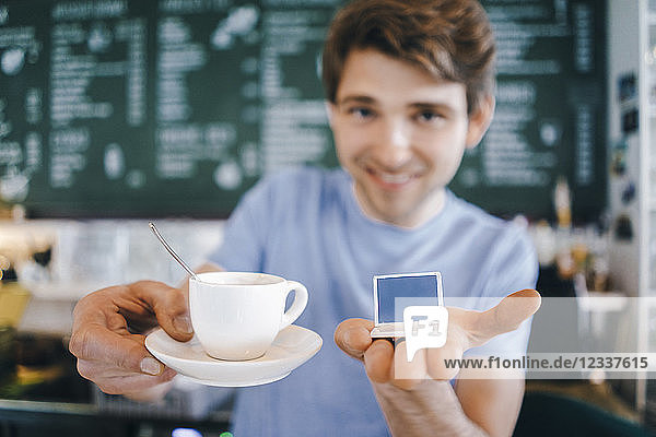 Smiling man in a cafe offering cup of coffee and holding miniature laptop model