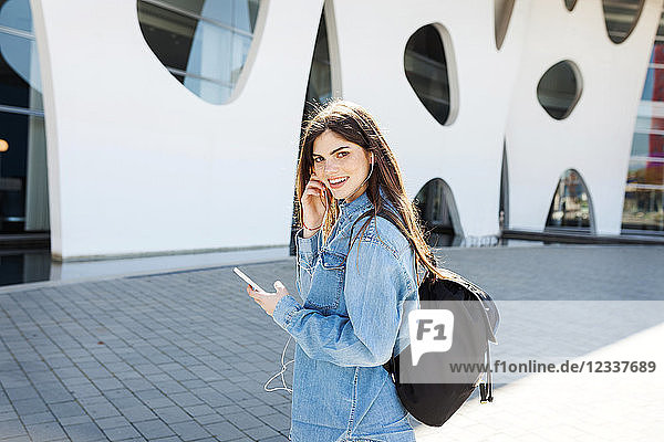 Spain  Barcelona  portrait of smiling young woman with backpack listening music with cell phone and earphones