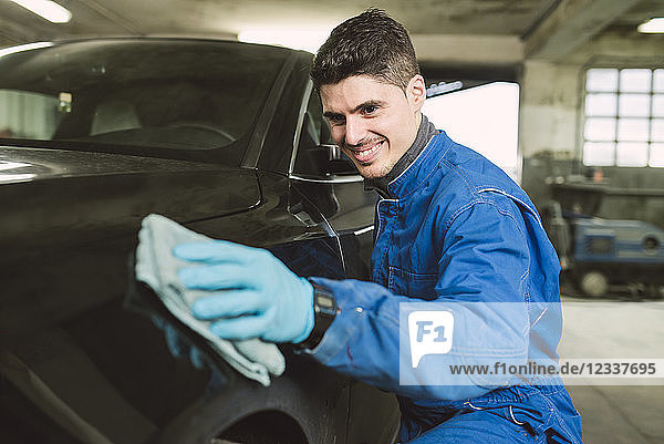 Smiling man cleaning a car in a workshop