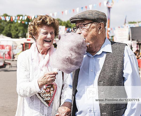 Senior couple on fair enjoying cotton candy