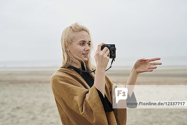 Netherlands  portrait of blond young woman with camera on the beach
