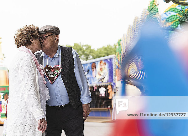 Senior couple with gingerbread heart kissing on fair