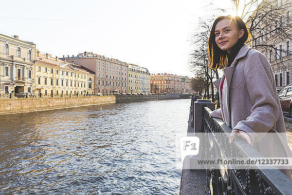 Russia  St. Petersburg  young woman next to a canal