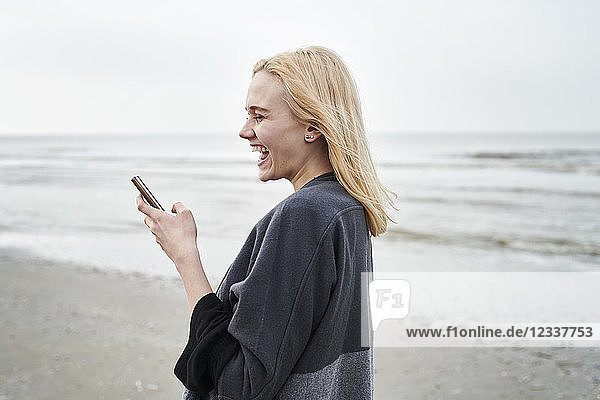 Netherlands  laughing blond young woman using smartphone on the beach