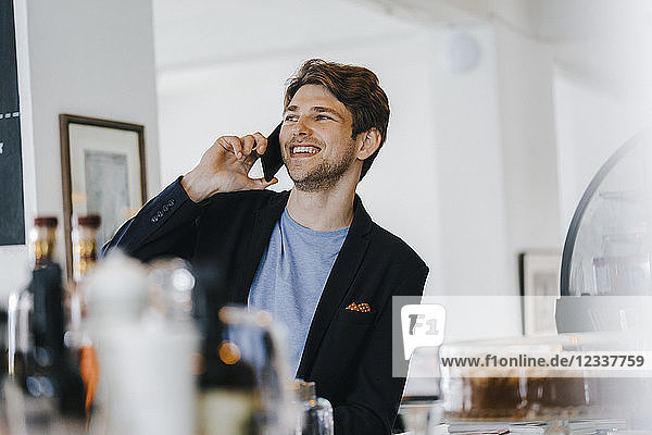 Smiling man in a cafe talking on cell phone