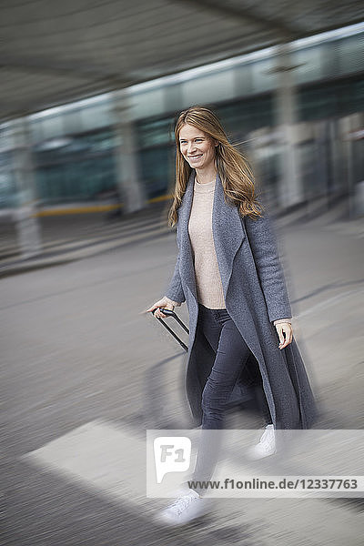 Confident businesswoman pulling suitcase at airport