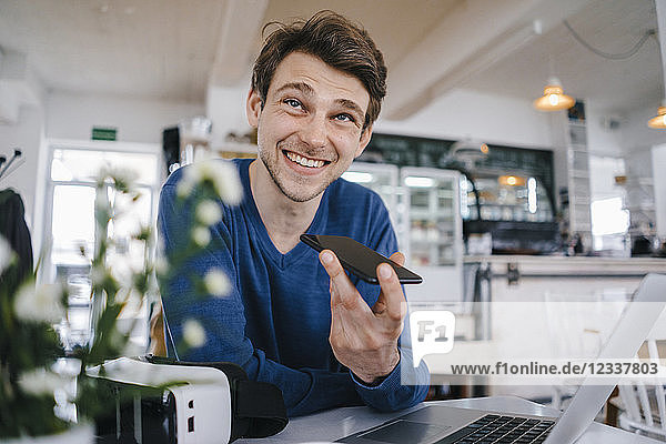 Smiling man in a cafe with cell phone and laptop