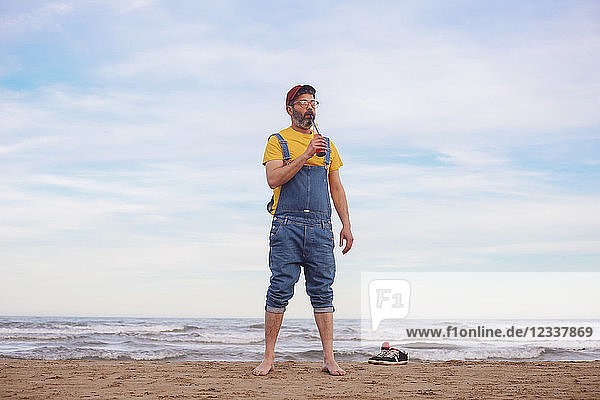 Bearded man drinking soft drink on the beach