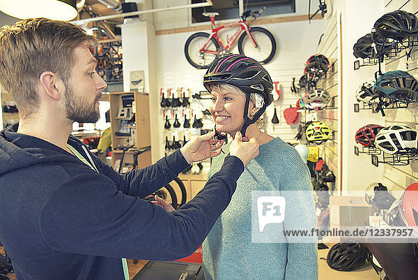 Salesperson helping customer with bicycle helmet